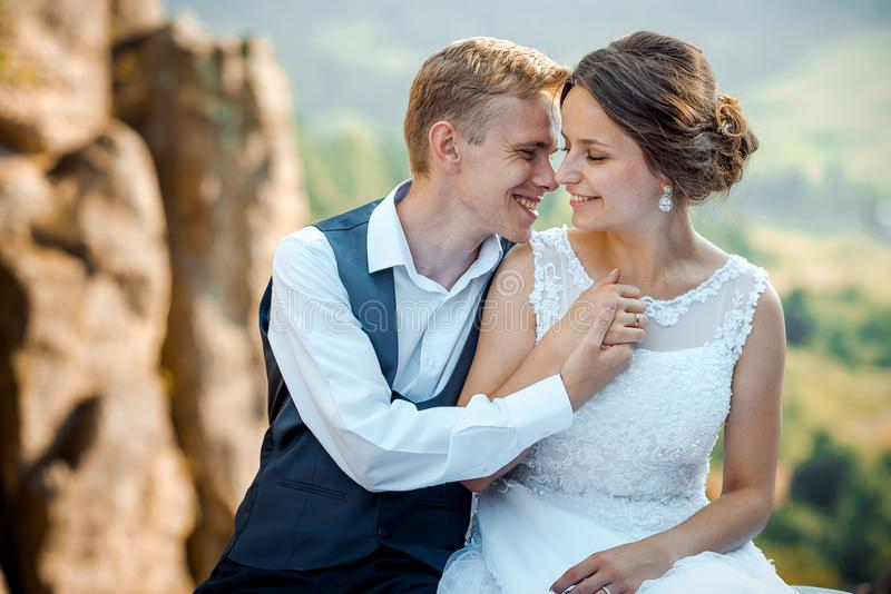 Emotional wedding portrait. Beautiful young newlywed couple is pretty smiling, tenderly holding hands and rubbing noses royalty free stock image