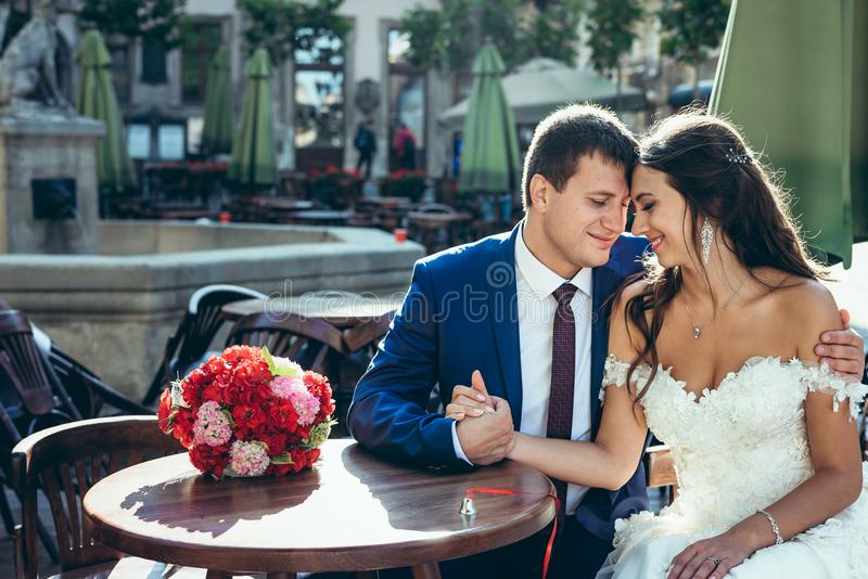 Emotional wedding portrait of the happy newlyweds holding hands and touching heads while sitting at the wooden table royalty free stock photos