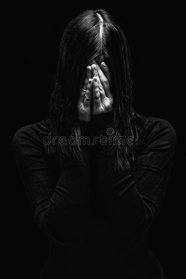 Emotional woman crying and covering the face with the hands hiding the tears stock image