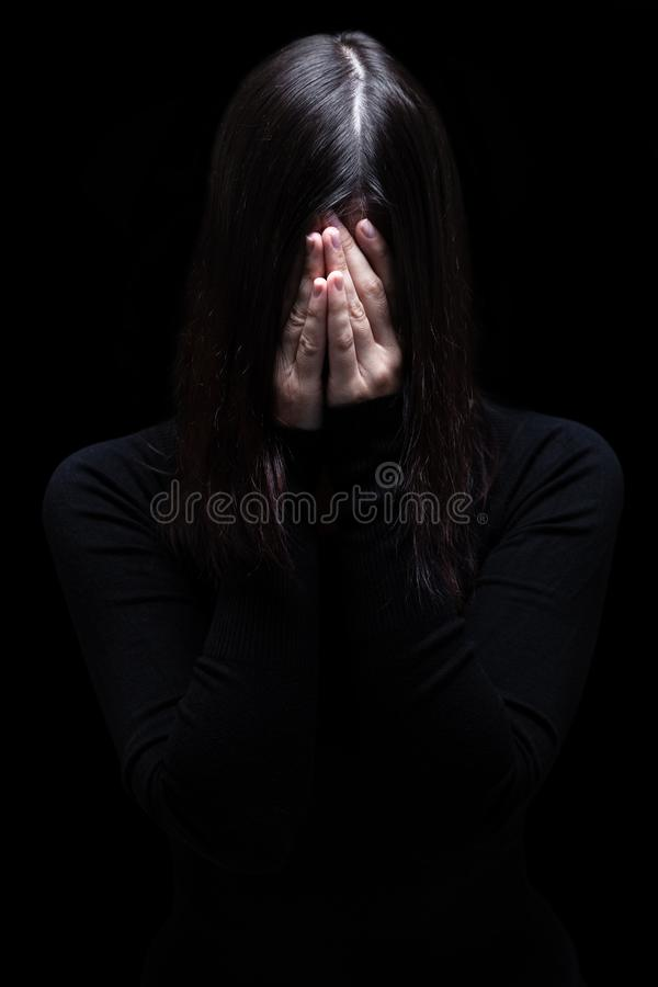 Emotional woman crying and covering the face with the hands hiding the tears stock photo