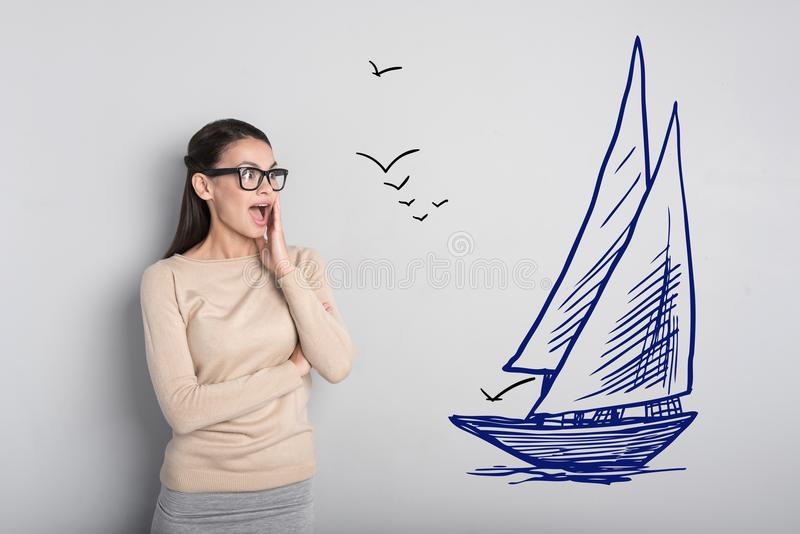 Emotional woman feeling impressed while noticing a big ship stock photography