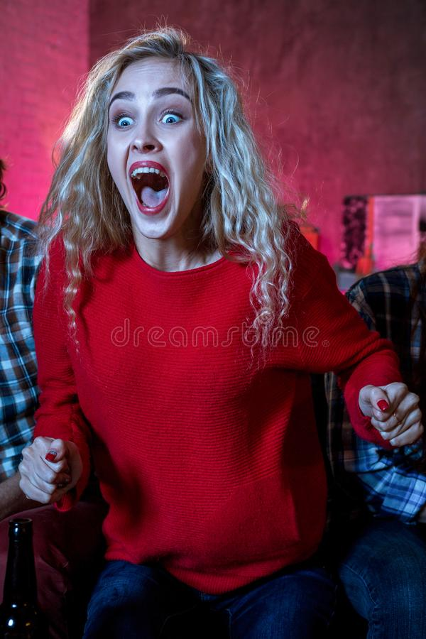 Emotional woman football fan at home sofa couch watching excited. Television soccer game, eating popcorn, cheering and supporting favorite team stock photo