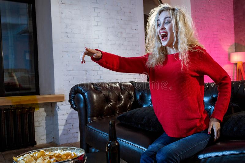 Emotional woman football fan at home sofa couch watching excited. Television soccer game, eating popcorn, cheering and supporting favorite team royalty free stock photo