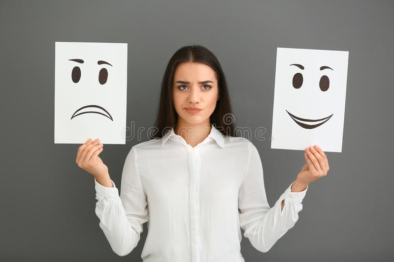 Emotional woman holding sheets of paper with drawn emoticons on grey background royalty free stock image