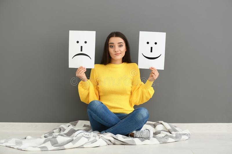 Emotional woman holding sheets of paper with drawn emoticons while sitting near grey wall royalty free stock photo