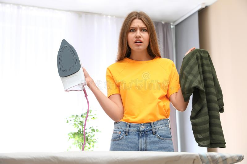 Emotional woman with iron and clothes. At home royalty free stock image
