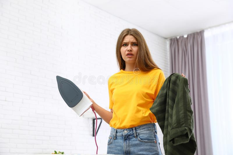 Emotional woman with iron and clothes. At home stock image