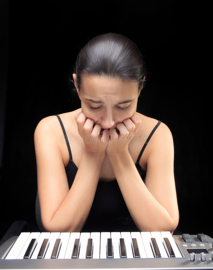 Emotional woman learning to play the piano. royalty free stock images