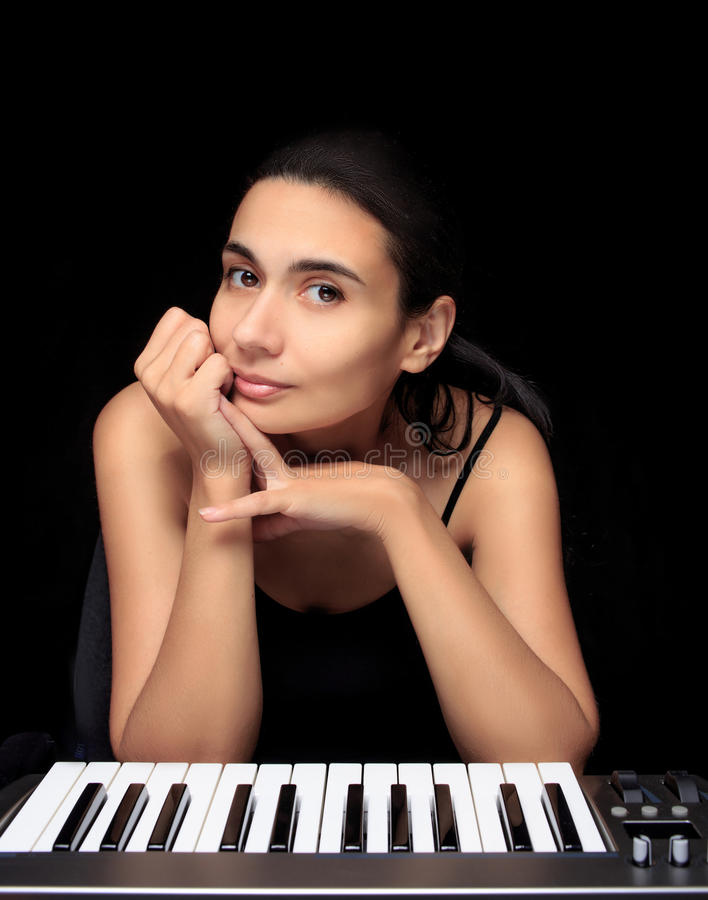 Emotional woman learning to play the piano. royalty free stock photography