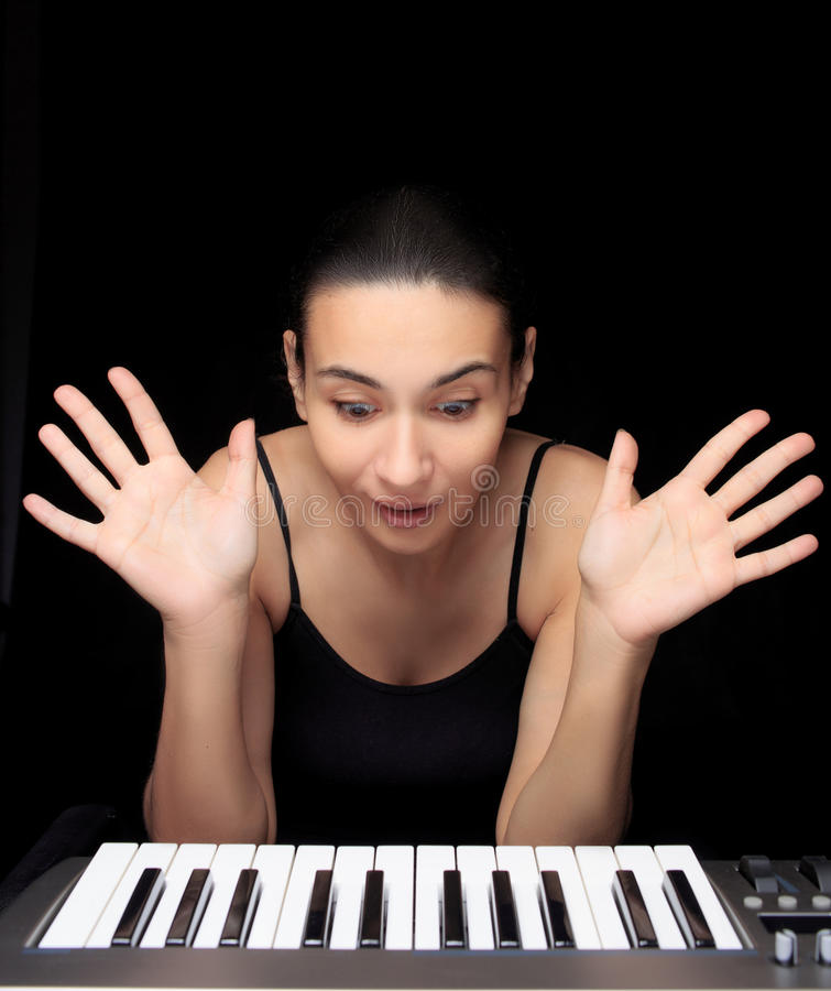 Emotional woman learning to play the piano. stock photos