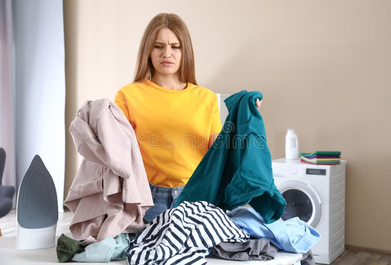 Emotional woman near board with iron and pile of clothes. In bathroom stock image