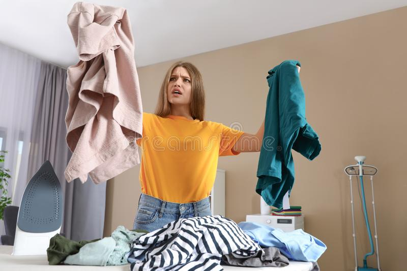 Emotional woman near board with iron and pile of clothes. At home stock image