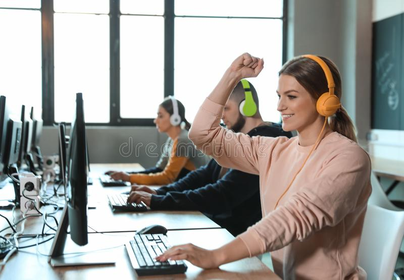 Emotional woman playing video game in cafe. Emotional women playing video game in internet cafe royalty free stock image