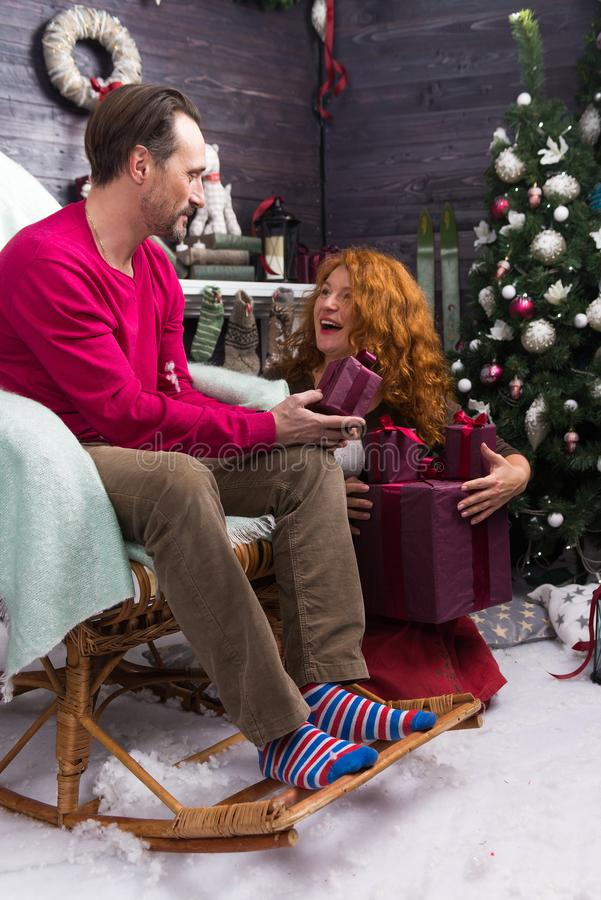 Excited woman holding gift boxes and looking at her calm husband. Emotional women sitting near the Christmas tree and looking at her husband in the rocking chair stock photography