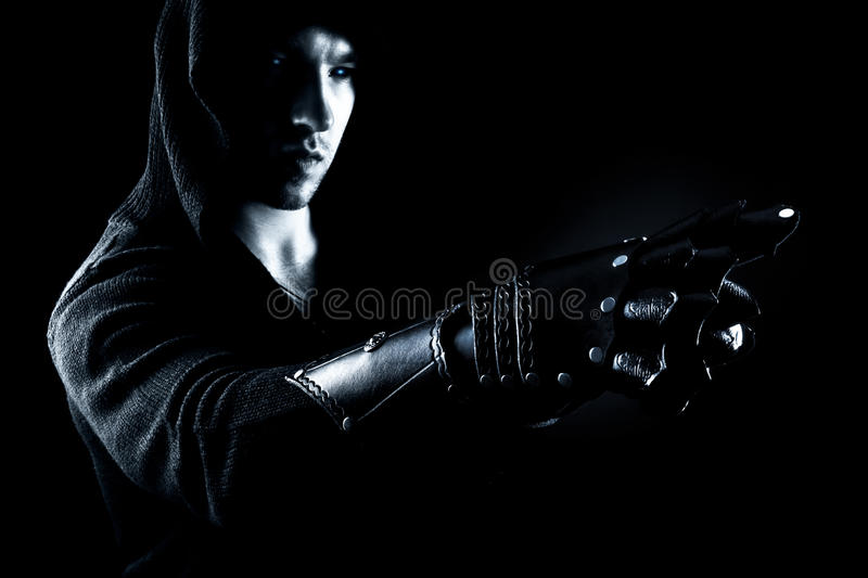 Emotional, young and attractive assassin in gloves on the black background. royalty free stock image