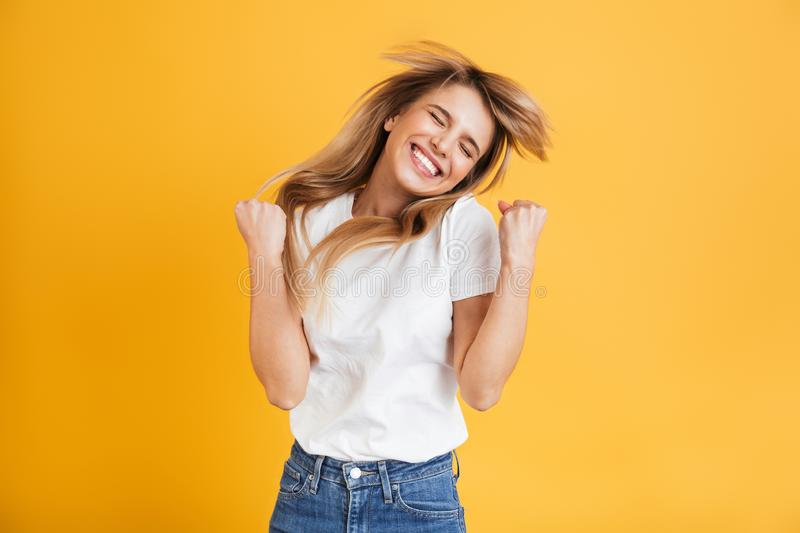 Emotional young blonde woman posing isolated over yellow wall background dressed in white casual t-shirt showing winner gesture. Image of a happy emotional young royalty free stock images