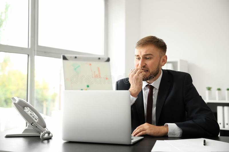 Emotional young businessman after making mistake while working with laptop in office stock image