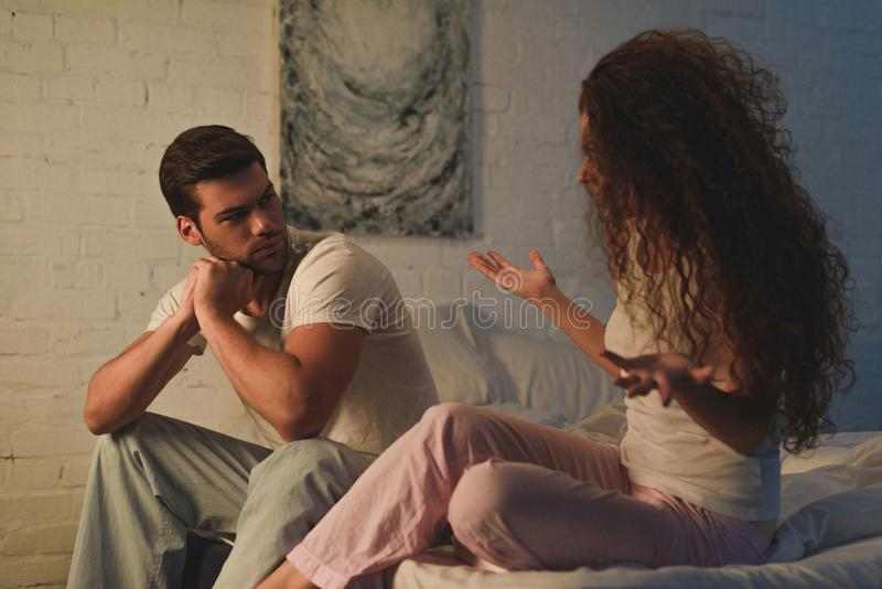 Emotional young couple in pajamas quarreling on bed relationship difficulties. Concept stock photo