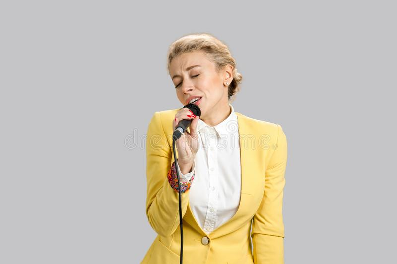Emotional young lady singing into microphone. stock image