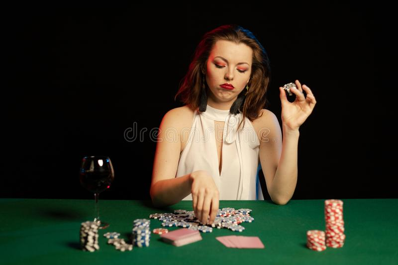Emotional young lady in a white blouse drinking wine from a glass and playing cards. On a table on green cloth in a casino royalty free stock photo