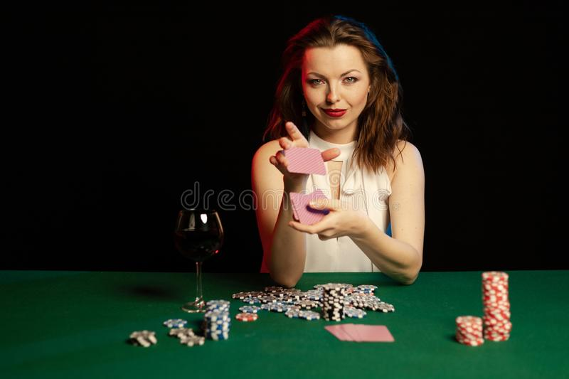 Emotional young lady in a white blouse drinking wine from a glass and playing cards. On a table on green cloth in a casino stock photos