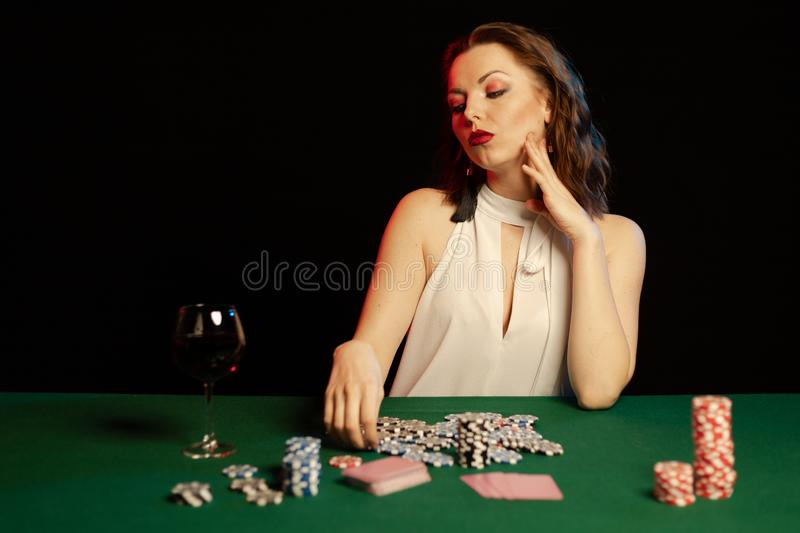 Emotional young lady in a white blouse drinking wine from a glass and playing cards. On a table on green cloth in a casino royalty free stock photos