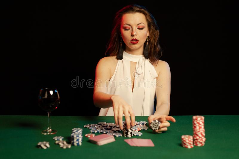 Emotional young lady in a white blouse drinking wine from a glass and playing cards. On a table on green cloth in a casino royalty free stock images