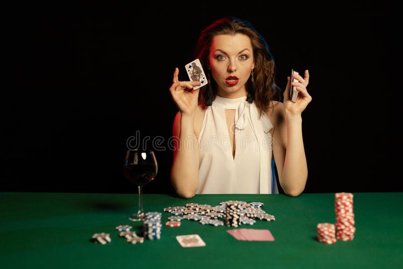 Emotional young lady in a white blouse drinking wine from a glass and playing cards. On a table on green cloth in a casino royalty free stock photography