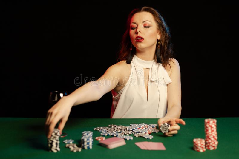 Emotional young lady in a white blouse drinking wine from a glass and playing cards. On a table on green cloth in a casino stock images