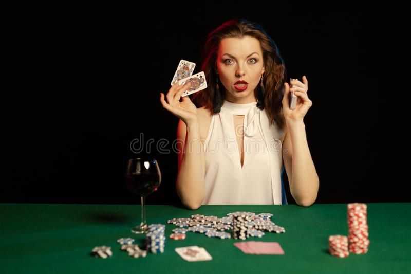 Emotional young lady in a white blouse drinking wine from a glass and playing cards. On a table on green cloth in a casino stock photography