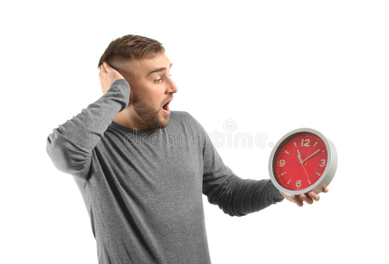 Emotional young man with clock on white background royalty free stock photo