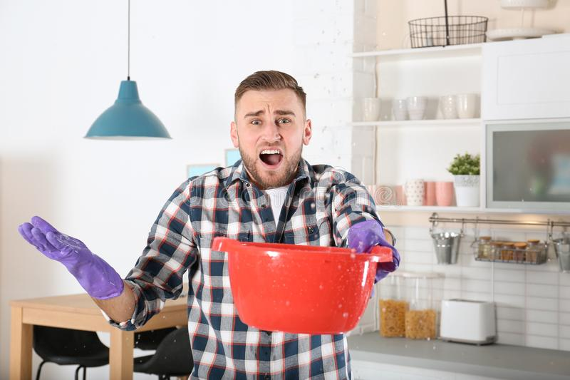 Emotional young man holding plastic basin under water leakage from ceiling in kitchen. Plumber service stock image