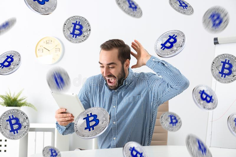 Emotional young man with tablet celebrating victory. In office royalty free stock image