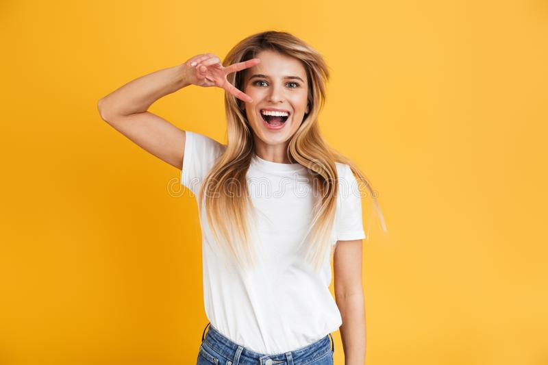 Emotional young pretty blonde woman posing isolated over yellow wall background dressed in white casual t-shirt showing peace. Image of a cheerful emotional stock photos