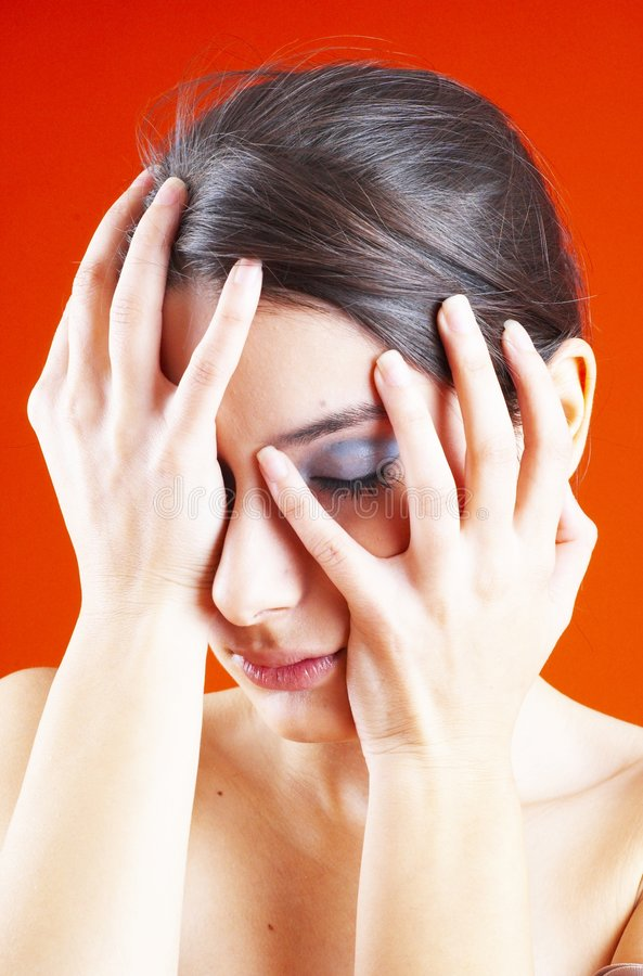 Emotional Young Woman. A studio portrait of a young woman, holding her hands to her face, experiencing several different emotions royalty free stock photos