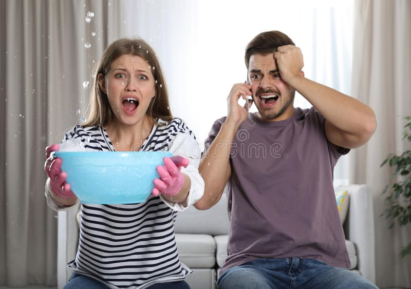 Emotional young woman collecting water leaking from ceiling while her husband calling plumber. In living room stock photography