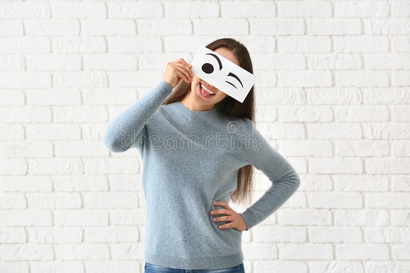 Emotional young woman hiding face behind sheet of paper with drawn eyes against white brick wall stock image