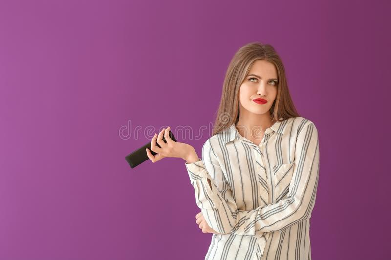 Emotional young woman with remote control on color background royalty free stock images