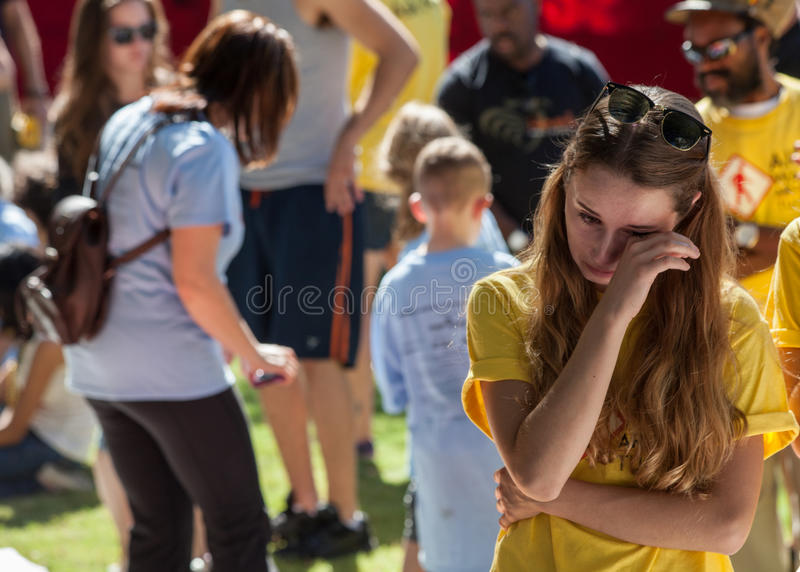 Emotional young woman viewing section of the AIDS Quilt royalty free stock image