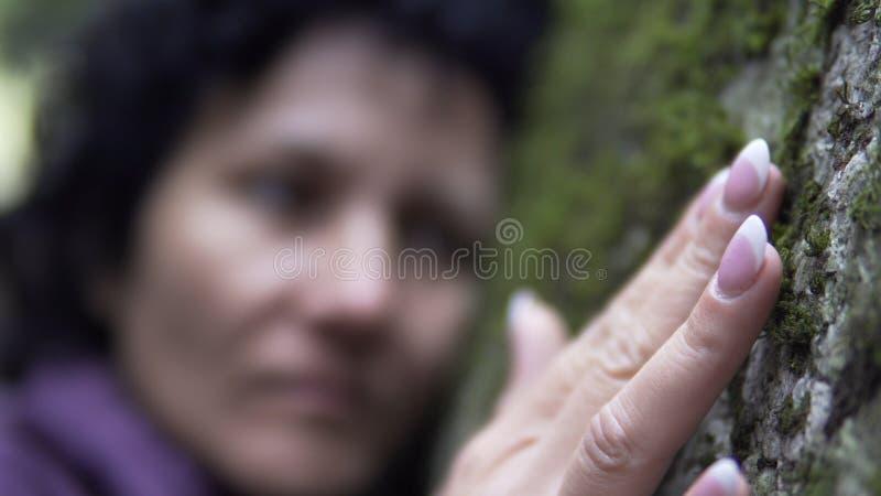 Emotionale Frau, die auf der Naturhand berührt das Steinmoos stillsteht stockbild