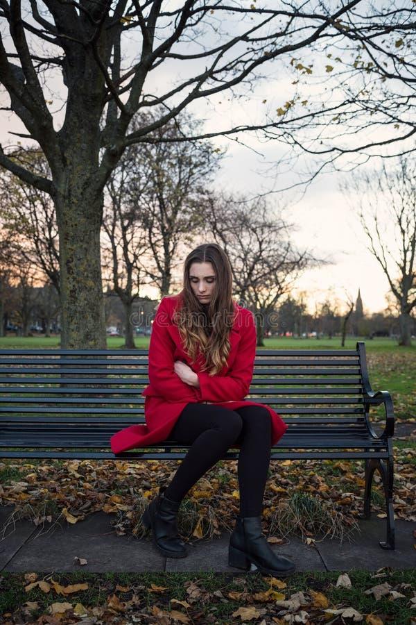 Emotionale junge Frau, die auf einer Parkbank sitzt stockfotografie