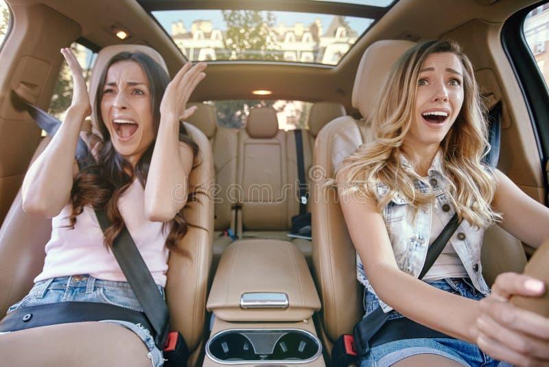 Emotionale junge Frauen, die in das Auto fahren stockfotografie