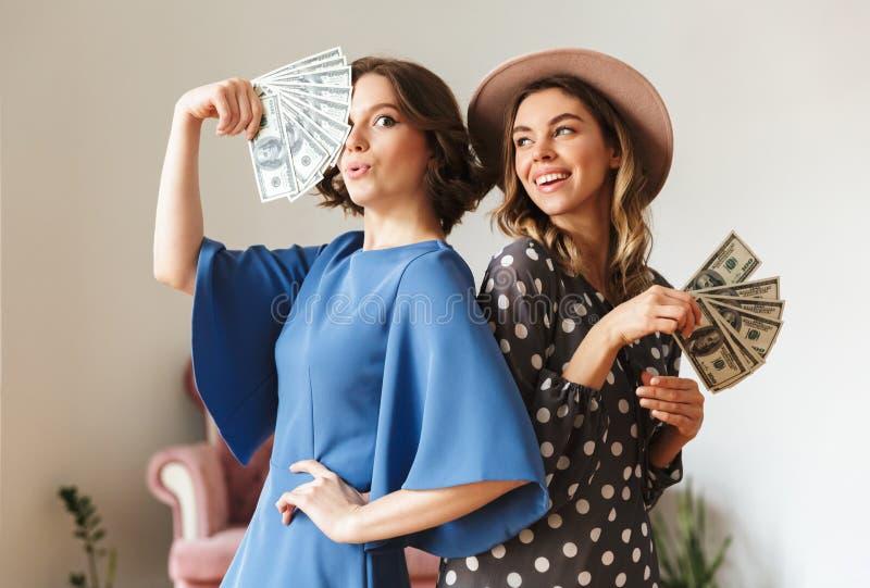 Emotionale junge Frauen, die zuhause Geld halten stockfoto