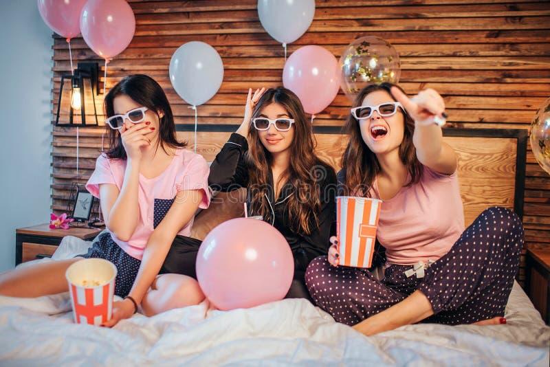 Emotionale junge Frauen sitzen auf Bett im festlichen Raum Sie passen Film durch spezielle Gläser auf Modelle tragen Pyjamas sie lizenzfreies stockfoto