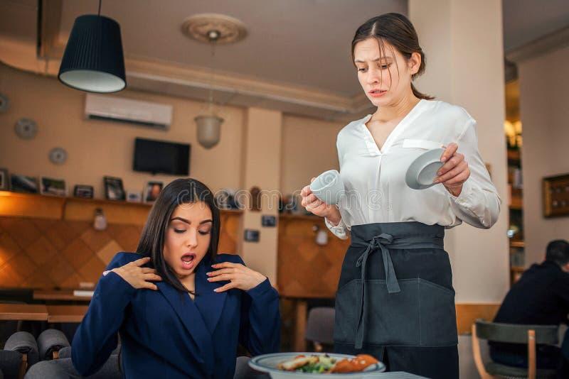 Emotionale junge Geschäftsfrau sitzen bei Tisch im Restaurant Sie wird überrascht und schaut unten Kellnerin gießen etwas Kaffee  lizenzfreies stockfoto