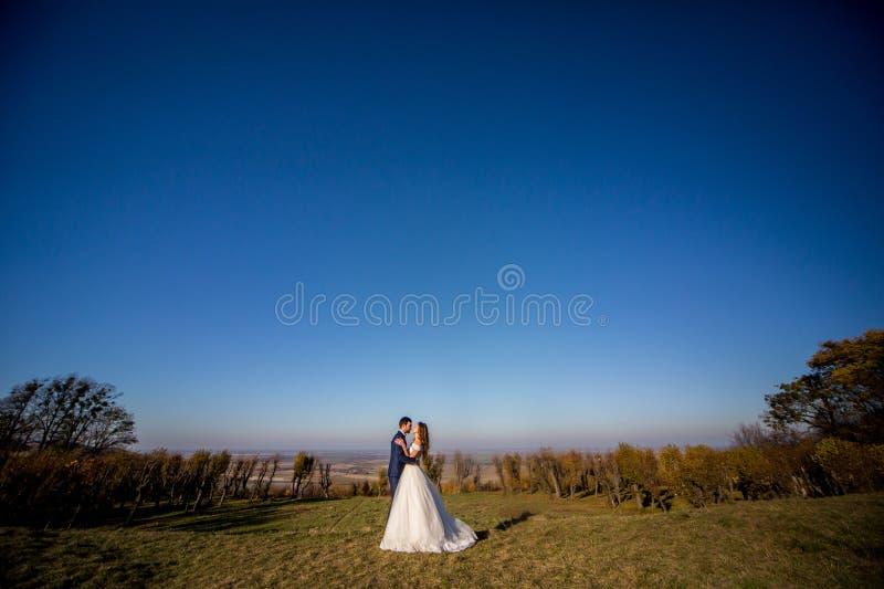 Emotionale schöne Braut, die Jungvermähltenbräutigam umarmt und küsst stockfoto