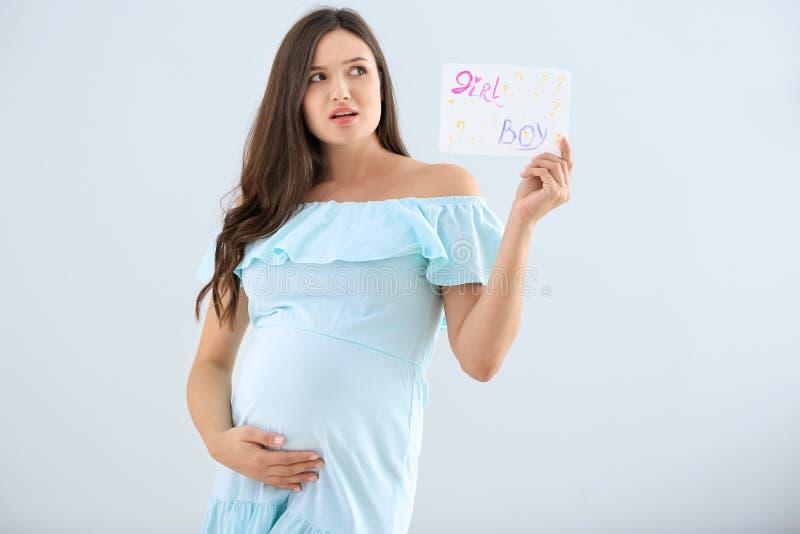 Emotionale schwangere Frau, die Papier mit Text JUNGEN hält? MÄDCHEN? auf hellem Hintergrund lizenzfreie stockfotos