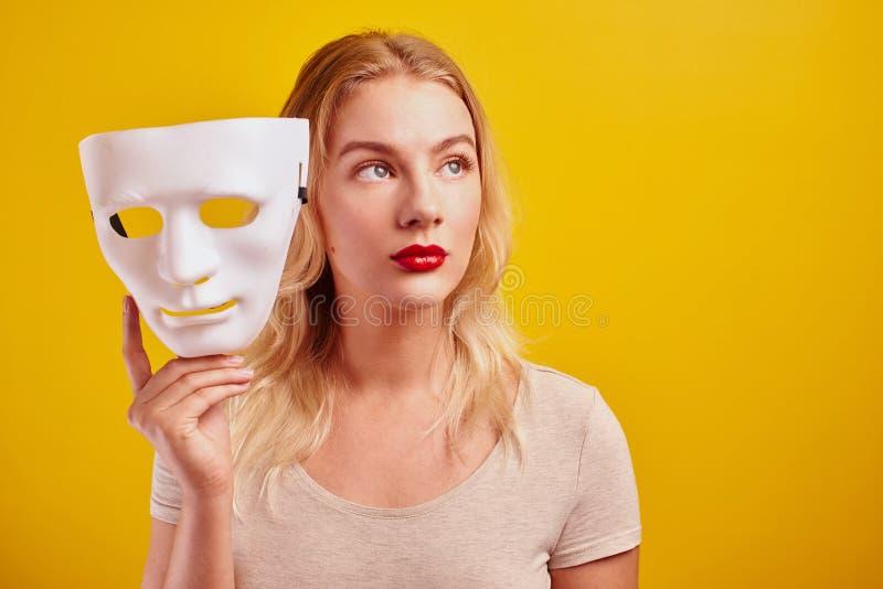 Emotionale weibliche Person mit weißer Maske auf gelbem Hintergrund Internet Betrug Konzept, anonym, inkognito, bipolare Persönli lizenzfreie stockfotografie