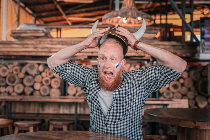 Emotionaler bärtiger Mann, der Viking-Hut schreit trägt, das Spiel aufpassend lizenzfreie stockfotos