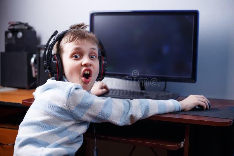 Emotionaler glücklicher Junge mit den Kopfhörern, die on-line-Computerspiel spielen stockfotografie